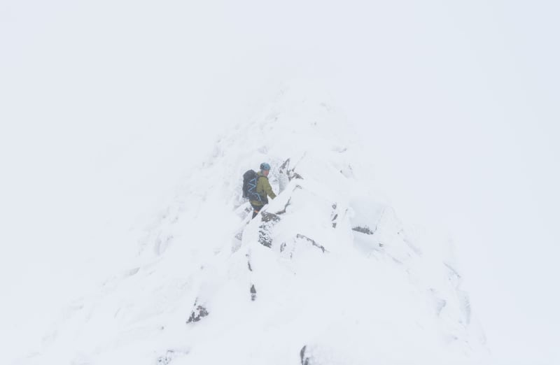 Chris on the CMD Arete. It's a near whiteout so you can only just see the rock-face in the middle.