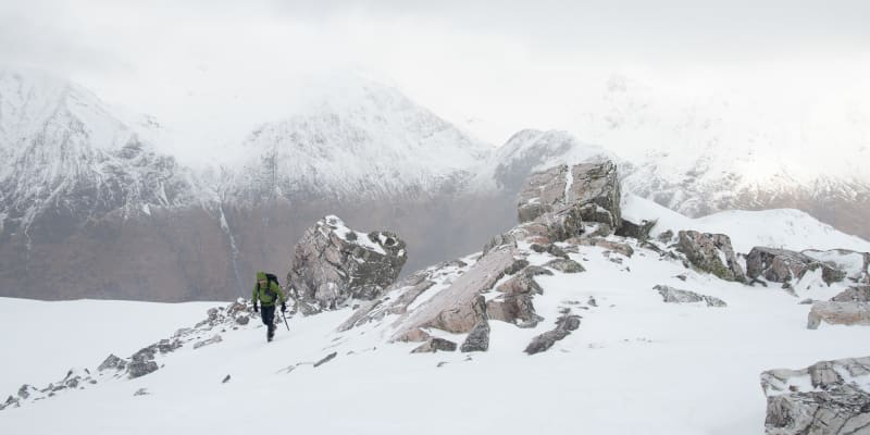 Ed ascending towards the camera. There's several large boulders partially covered in snow to the right.