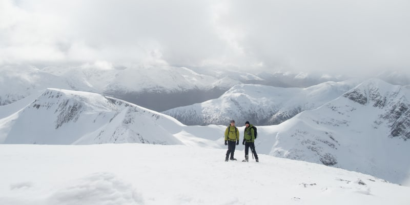 A portrait photo of Chris and Ed on top of a snowy mountain, with several other snowy summits visible behind.