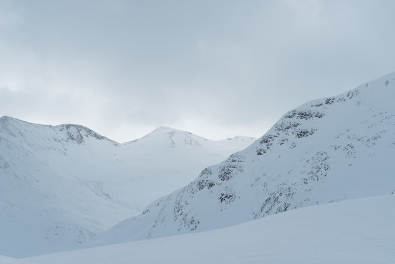 A low contrast view of several snowy ridges.