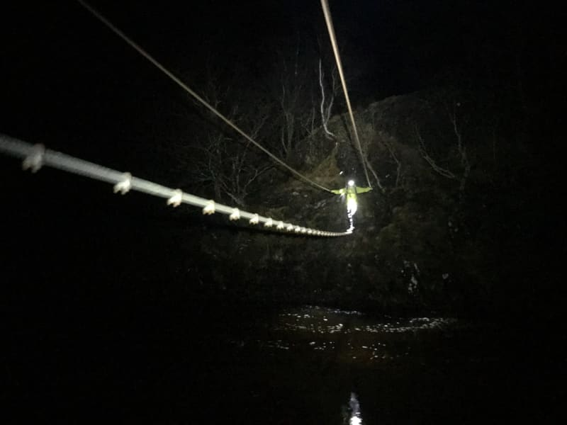 Chris crossing a rope bridge over a river, coming towards the camera. It's pitch black, and he's got a headtorch to lead the way.