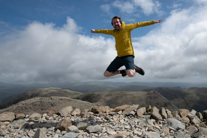 Ed jumping in the air on the summit of Scafell Pike.