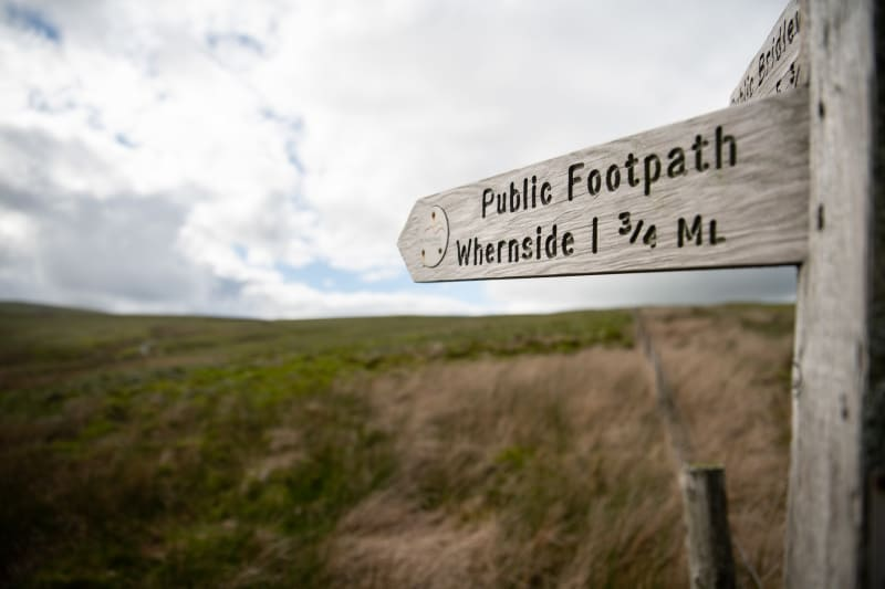A footpath sign points from right to left, marking the summit of Whernside, 1.75 miles away.