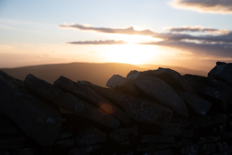 A close photo of the top row of stones of a stone all. The stones all lean to one side. In the background the sun is just setting.