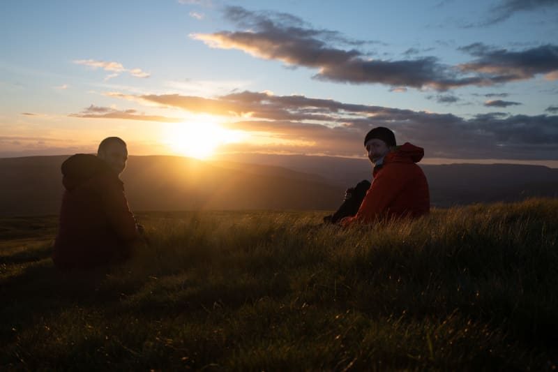 Ed and Chris sit on long grass in late golden sunset.