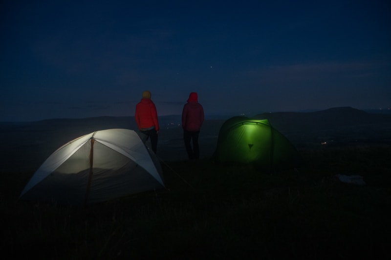 Ed and Chris stand still in the dark next to their tents. Each tent glows slightly from within.