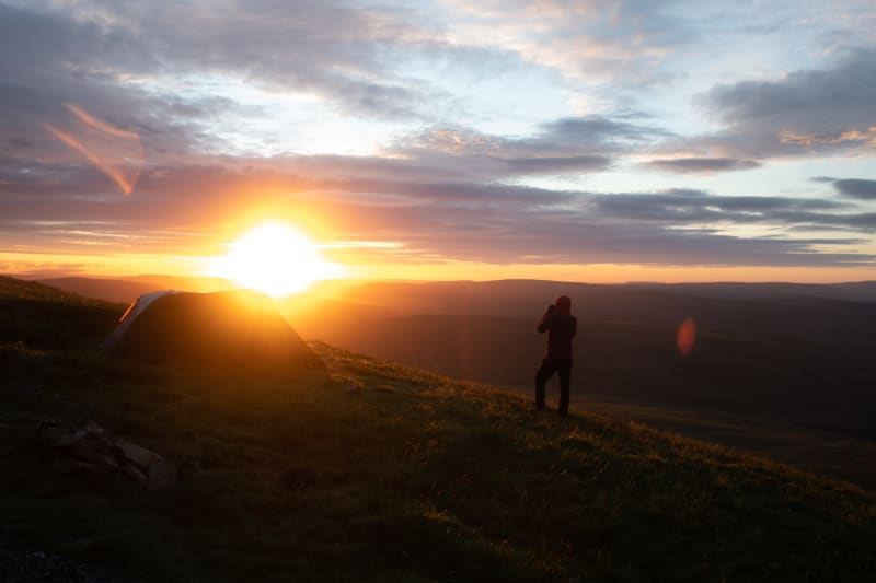 Sunrise over Whernside. Chris stands in the foreground in silhouette, taking a photo of the sun.