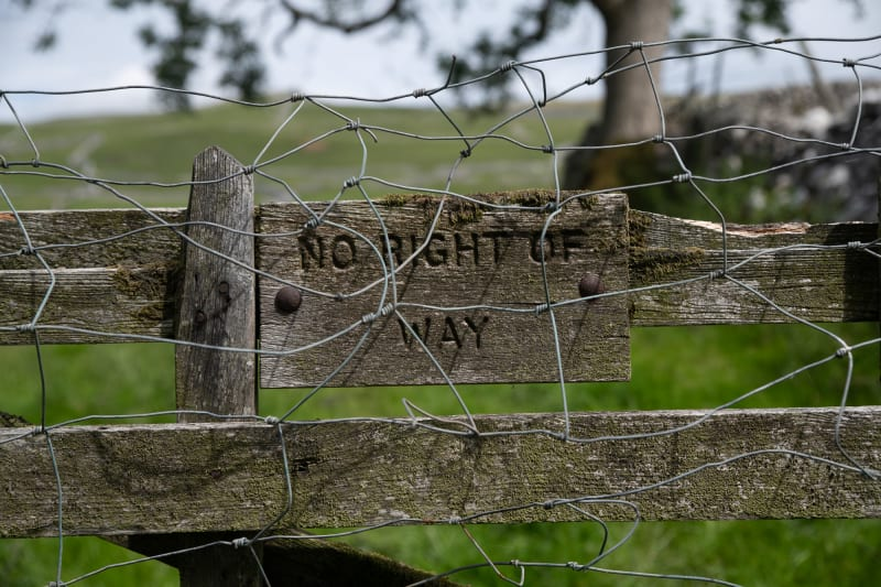 An aged wooden sign on a fence says 'No right of way' - it's also covered in chicken wire.