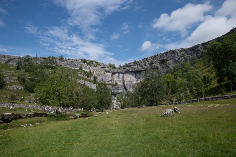 The face of Malham Cove as seen from a distance on a sunny day.