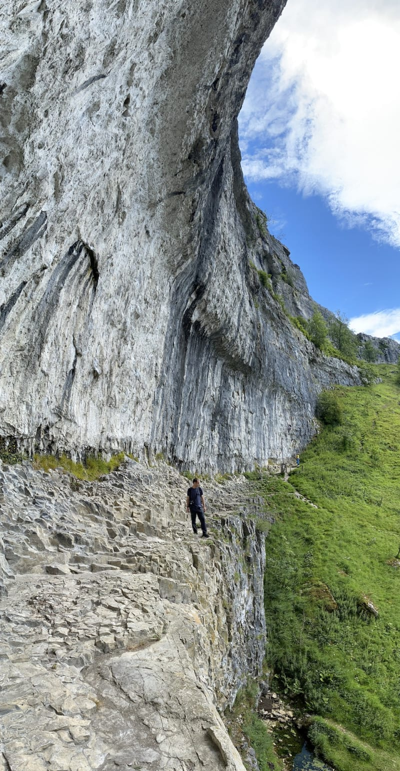 A vertical panorama from the side of Malham Cove. A large rock face looms over Chris.