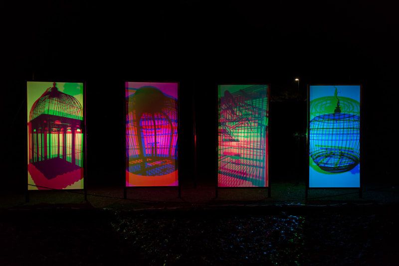 Four vertical panels are side by side in the dark. They're light from behind with bright neon colours, projected with shadows of birdcages.