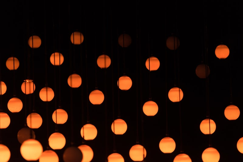 Orange balls of light hand suspended from darkness