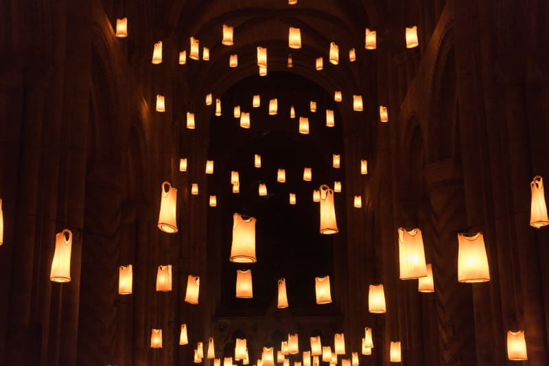 The vast hall of Durham Cathedral at night. The hall is filled at various levels by warm hanging lights. On closer inspection, the lights are made from white vests lit from within.