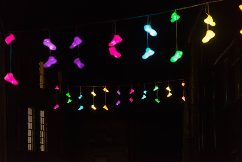 Pairs of brightly coloured lights in the shape of shoes dangle from a line suspended between two rows of houses.