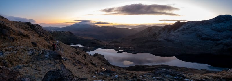 A panorama taken from midway up Snowdon before sunrise. The sky is lightening, but the landscape is still dark.