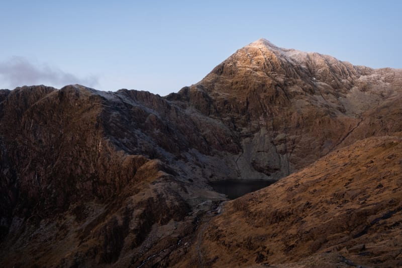 The jagged face of snowdon before sunrise. The mountain has a light dusting of snow on the top.