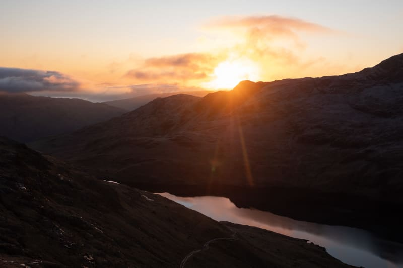 A sunrise photo taken from midway up Snowdon, facing the sun. There's a still lake on the bottom, reflecting some of the sunrise.