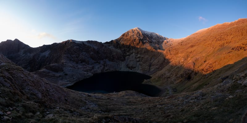 A panorama of the bowl of Snowdon taken just after sunrise. The right side of the mountain is bathed in orange sunlight, whilst the bowl and left are still in shadow.