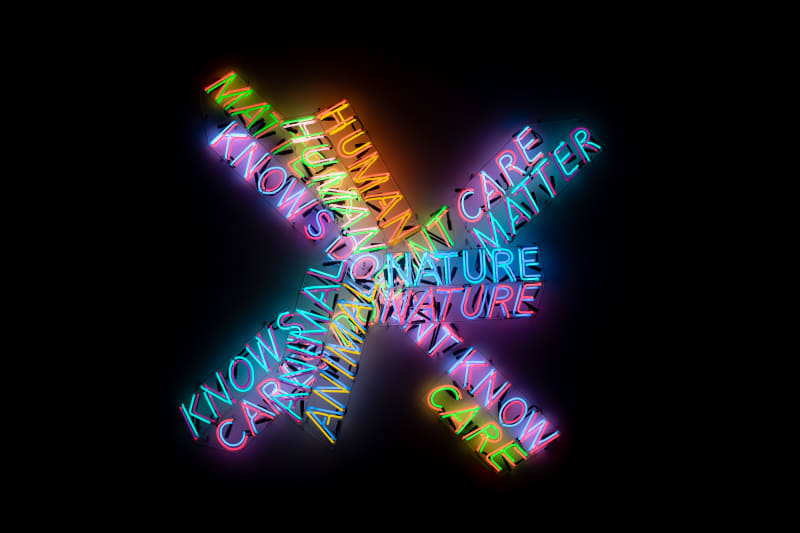 A large neon sculpture comprised of multiple overlaid words. All parts are lit up.