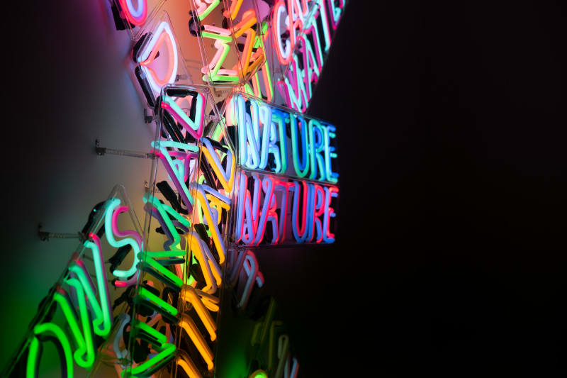 A large neon sculpture comprised of multiple overlaid words. The photo is taken from the side.