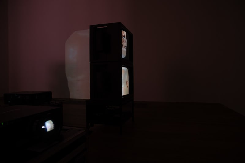 Two vintage television monitors are stacked vertically in a dark room, each showing a bald man's head. The same head is projected on the wall behind them.
