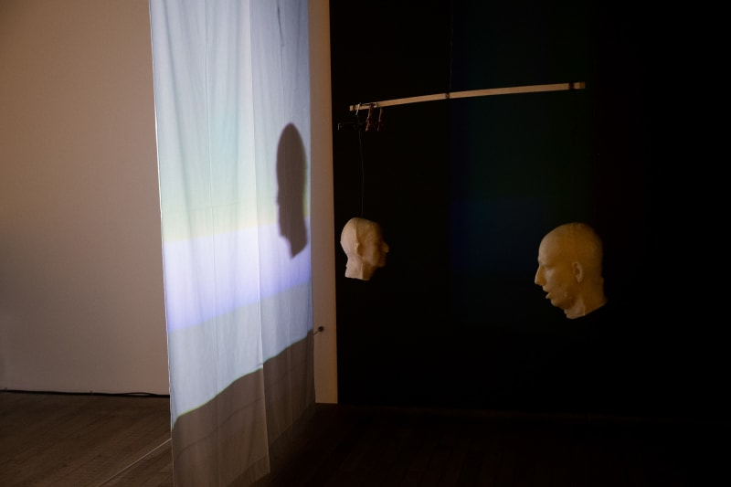 Two wax casts of a male head are suspended on either end of a mobile, in front of a dark background. A light from one side projects a shadow of another head on a nearby white sheet.