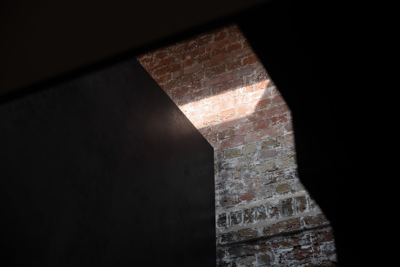 Looking through a void to an exposed brick wall, partially lit by sunlight.