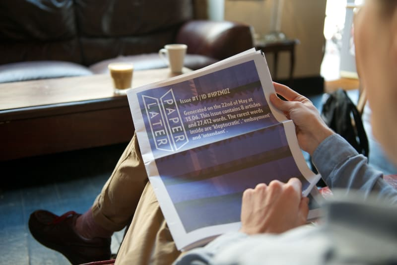 A man reading a PaperLater newspaper in a coffee shop.