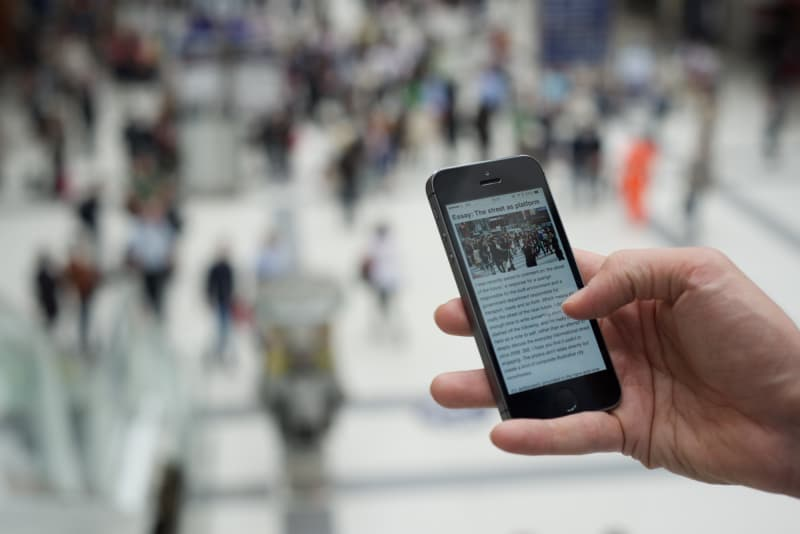 Photo of a hand holding a smartphone, which is showing a web article.