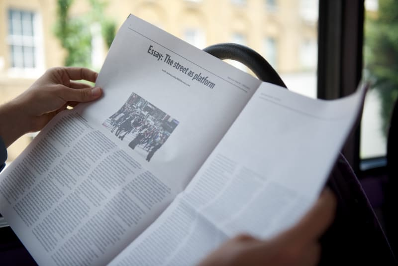 Photo of a PaperLater newspaper being read on a bus.