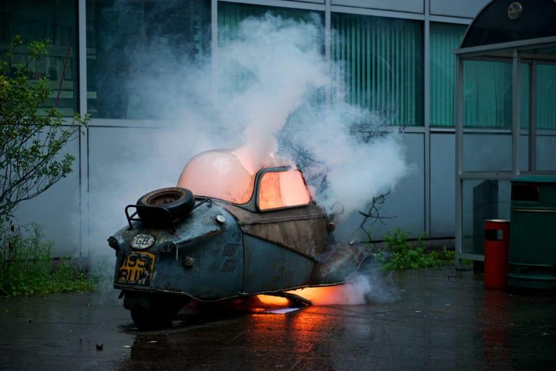 A Messerschmitt car on fire after being blown up.