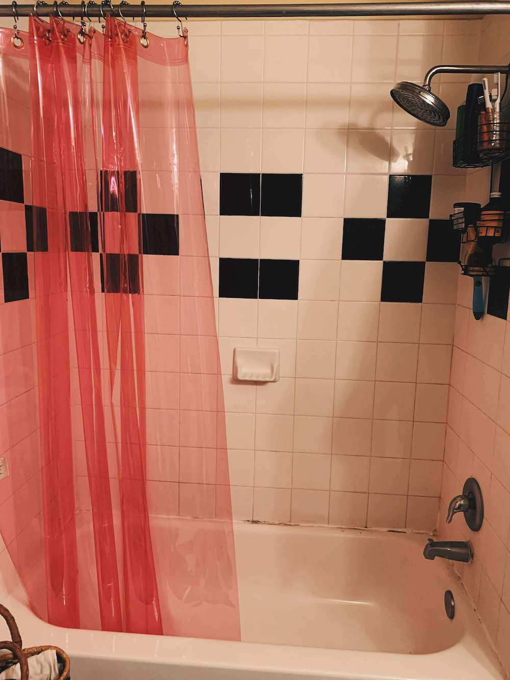 after shot of the shower with a hanging, brass shower organizer and a bright pink transluscent shower curtain