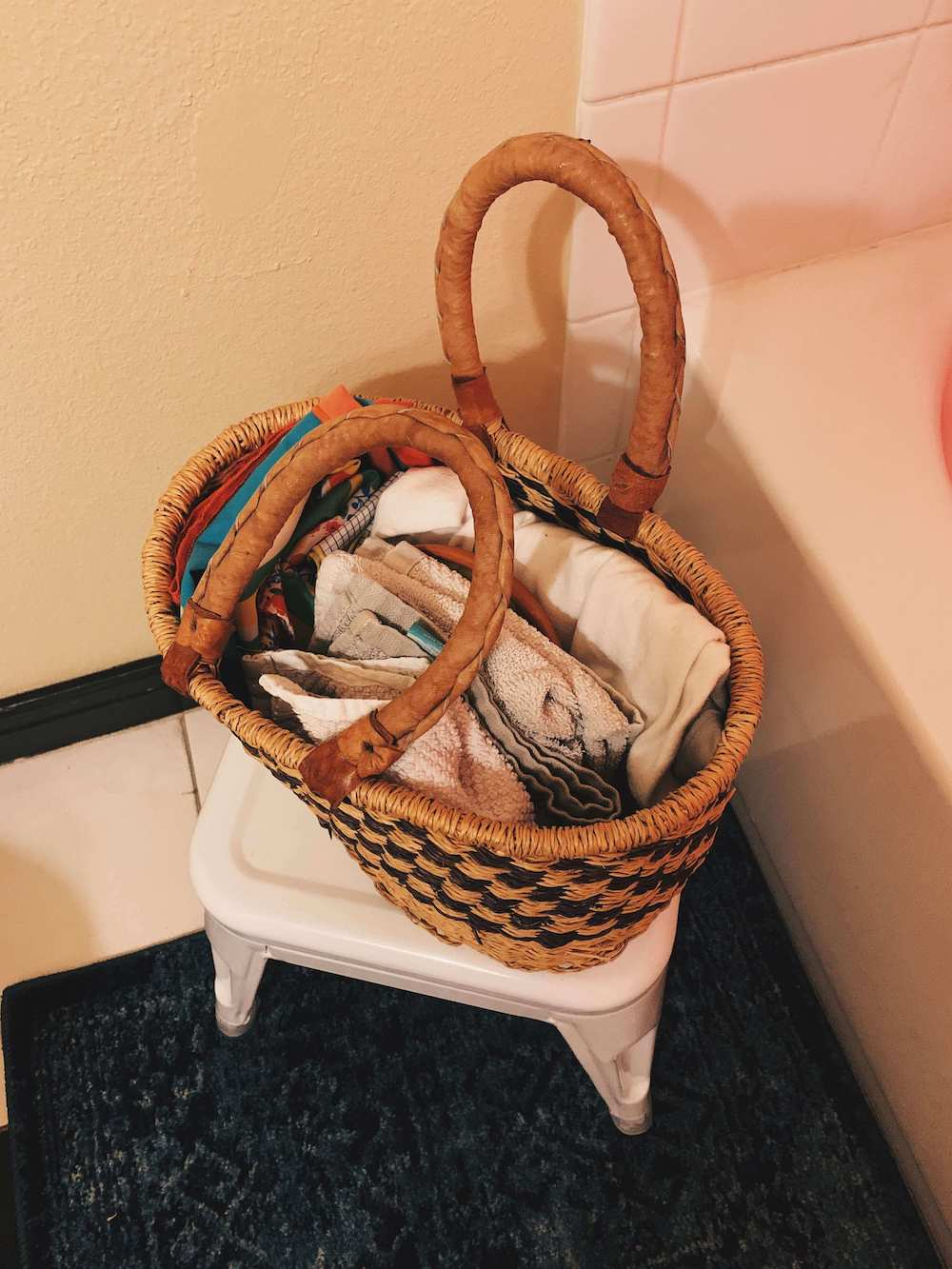 after shot of wicker basket on a white stool. the basket stores folded washcloths.