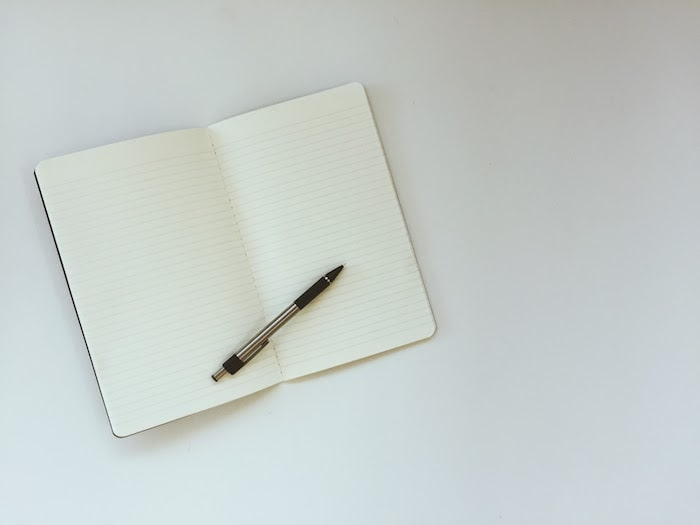 flat lay of a lined notebook and black pen on white background