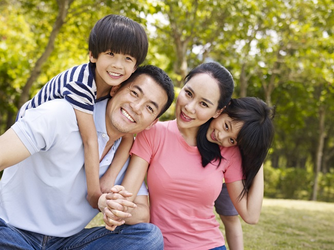 asian family with two children taking a family photo outdoors in a city park.