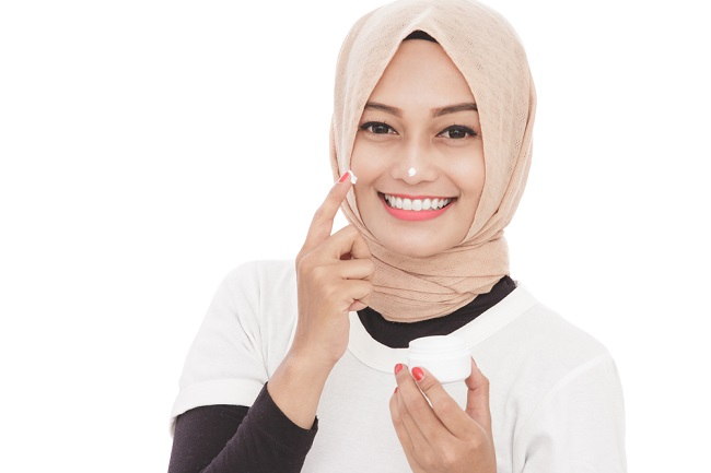 beautiful asian woman using moisturizer cream for face skin care
