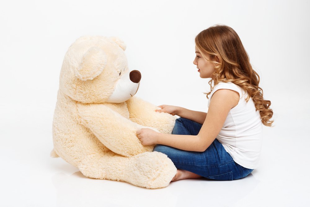 Adorable girl in casual clothes sitting on floor with toy bear, looking at him. White background
