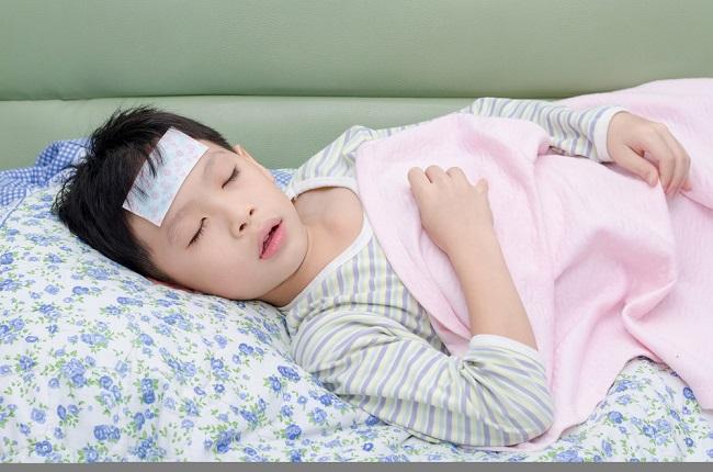 Little sick boy lying on bed