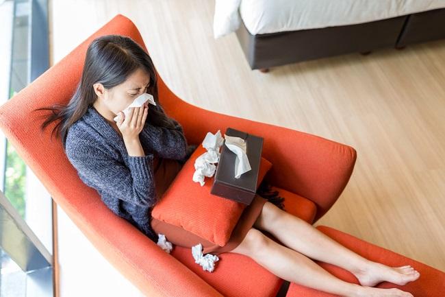 Woman sneezing at home - Oseltamivir