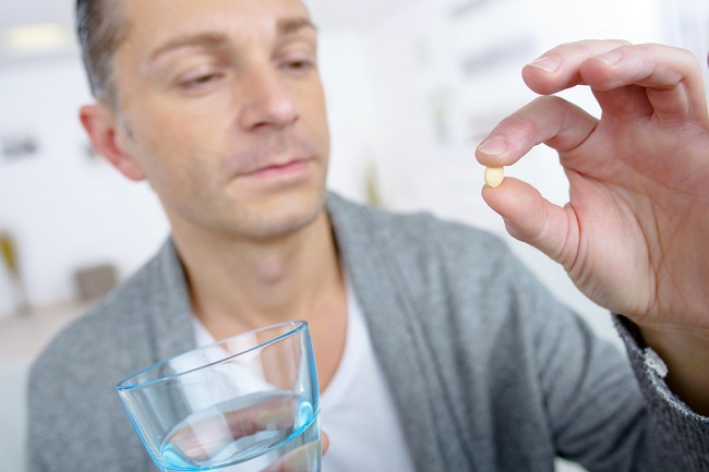 man taking a pill with glass of water