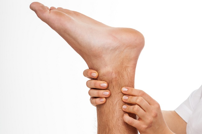 Physiotherapist palpating Achilles tendon
