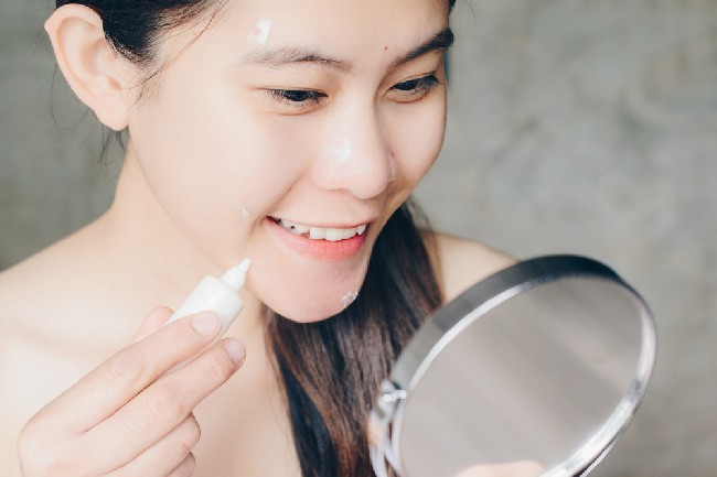 Portrait,Of,Young,Asian,Woman,Holding,Cosmetic,Tube,And,Applying