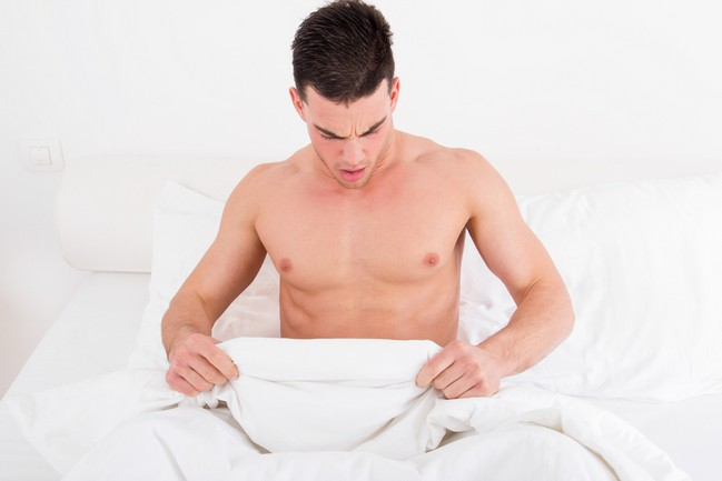Surprised,Half,Naked,Young,Man,In,Bed,Looking,Down,At