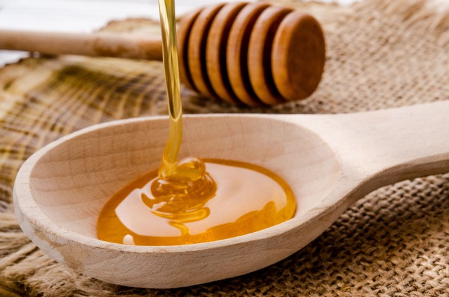Flowing,Fresh,Floral,Honey,On,A,Wooden,Spoon,In,A