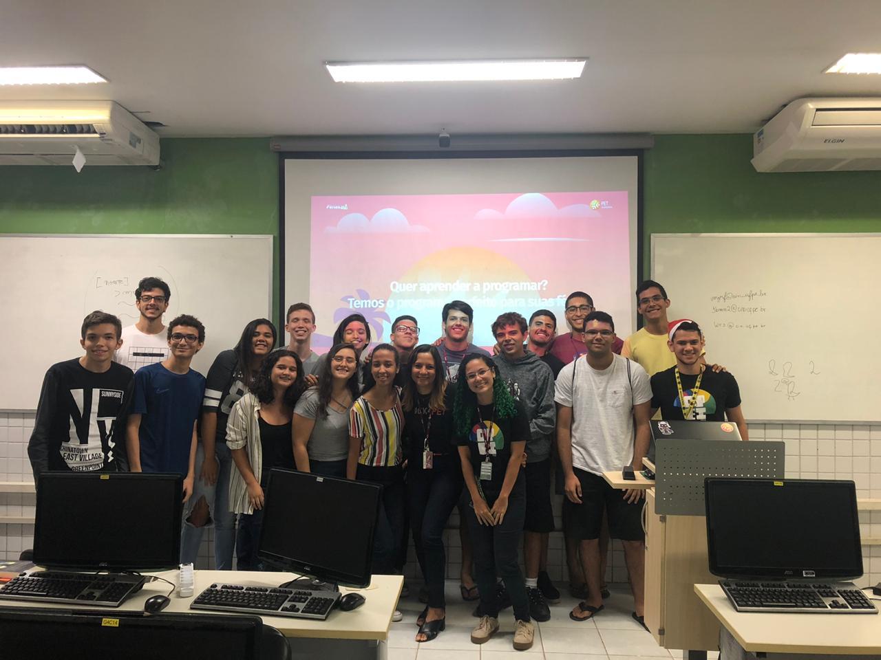 Integrantes do PET-Informática junto à estudantes de ensino médio que participaram do curso Férias.py. Ao fundo, o site do Férias.py projetado no quadro da sala.