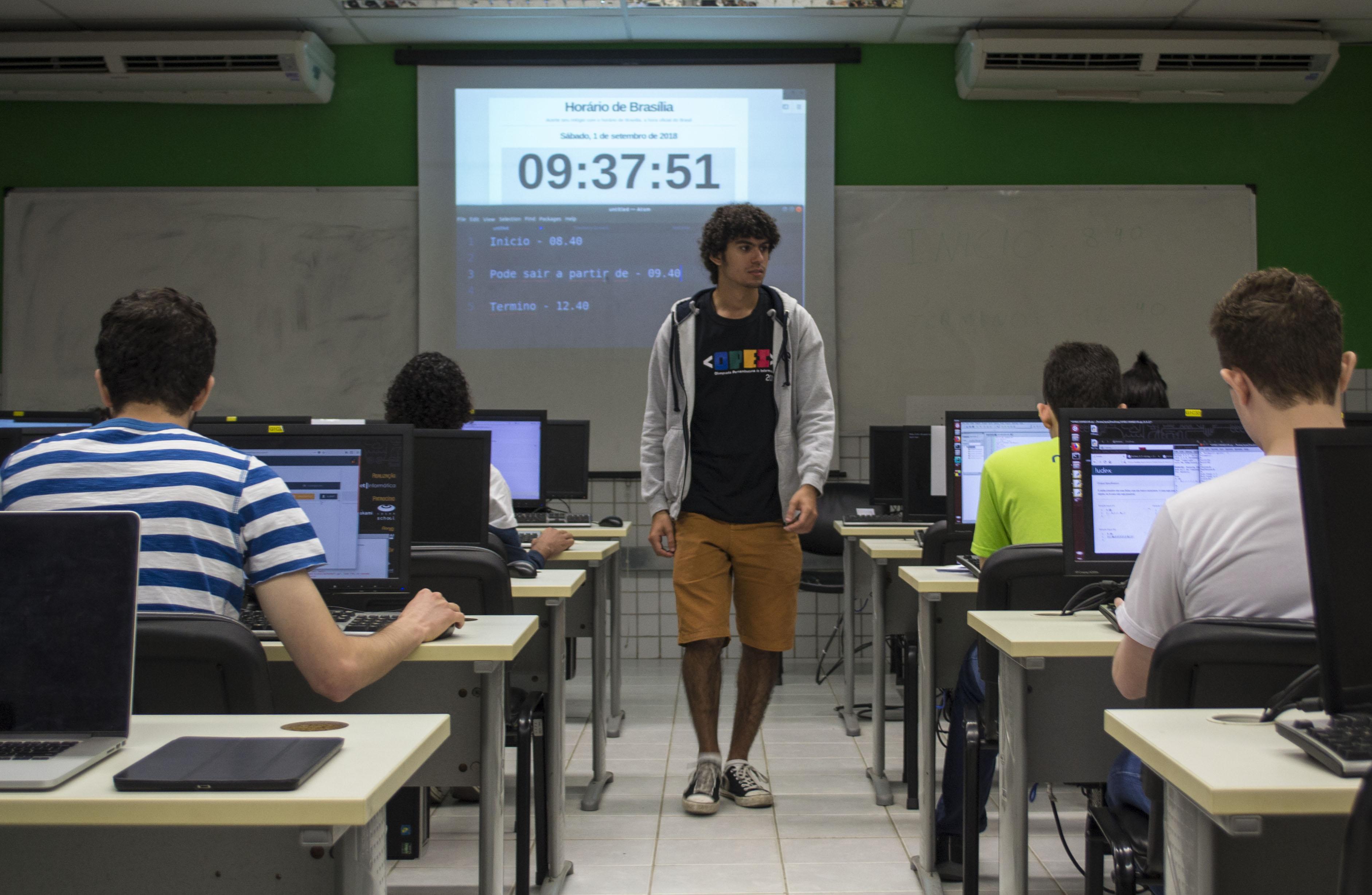 Sala com estudantes realizando a avaliação prática da OPEI em computadores. Ao centro, uma pessoa da equipe de voluntários da OPEI. Ao fundo, um relógio digital projetado no quadro da sala.