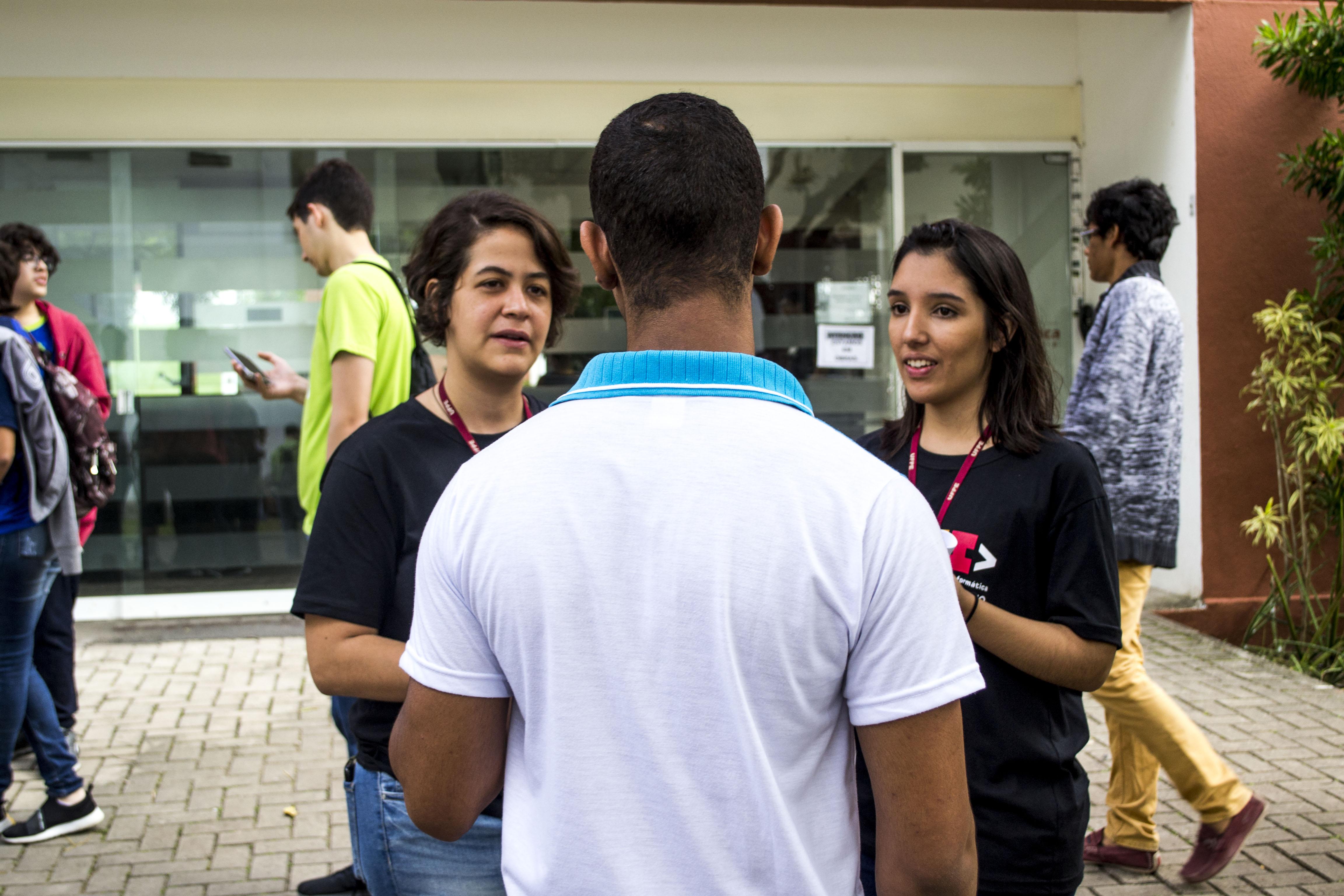 Duas petianas conversando com um participante da Olimpíada Pernambucana de Informática. Ao fundo, a entrada do Centro de Informática da Universidade Federal de Pernambuco e outras pessoas alunas.