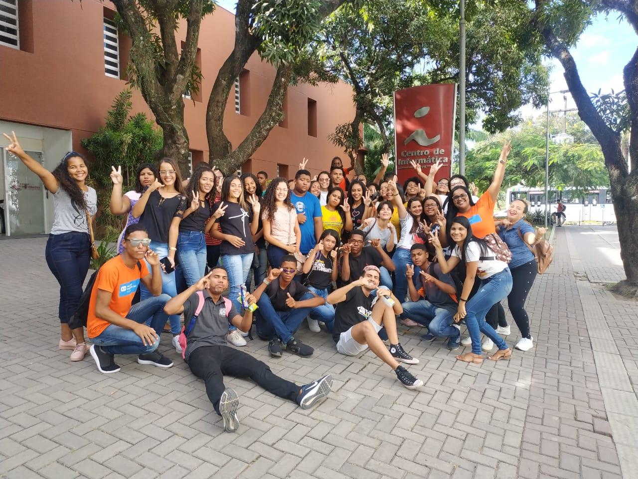 Estudantes e integrantes do PET-Informática em frente do Centro de Informática sorrindo e fazendo poses divertidas após uma visita.