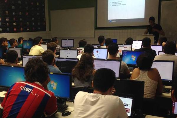 Estudantes em uma sala com computadores assistindo à uma workshop. Ao fundo, uma pessoa ministrando a workshop, com uma apresentação projetada no quadro da sala.