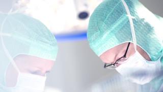 två kirurger i djup koncentration fotograferade i motljus